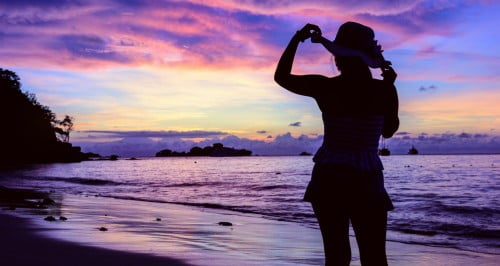 Femme sur la berge au soleil levant