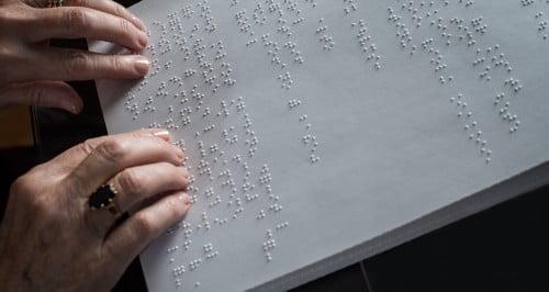 Mains sur une page de texte en braille