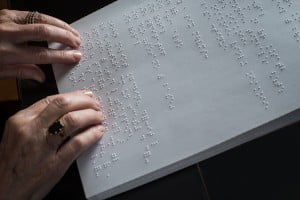 Photo : Mains de Nicole sur une page de texte en braille.