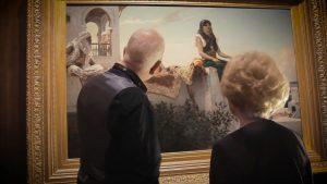 M. Martin et Nicole de dos regardant une toile, que M. Martin décrit.