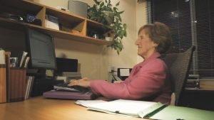 Nicole assise à son bureau