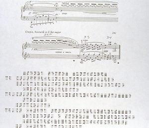 Photo de la partition standard ainsi que la partition en braille des 4 dernières mesures.