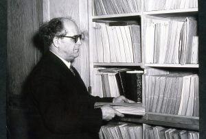 Photo de Armand Pellerin devant une bibliothèque
