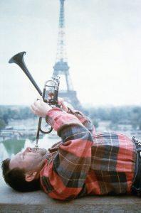Photo de Maurice Gourgues, couché sur le dos, jouant de la trompette, avec la Tour Eiffel en arrière plan.