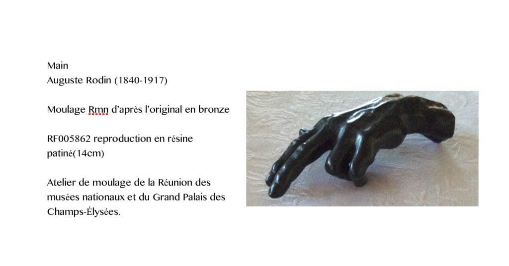 Main de Rodin, ouverte, présentée à l'horizontale, montrant le dos de la main. Et le texte suivant : Main, Auguste Rodin (1840-1917). Moulage Rmn d'après l'original en bronze. RF005862 reproduction en résine patiné (14 cm). Atelier de moulage de la Réunion des musées nationaux et du Grand Palais des Champs-Élysées.