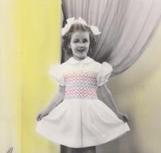 Nicole Trudeau a 5 ans, petite robe blanche et boucle dans les cheveux.